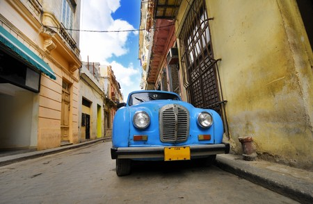 Colorful Havana building facades and old car parked in the street