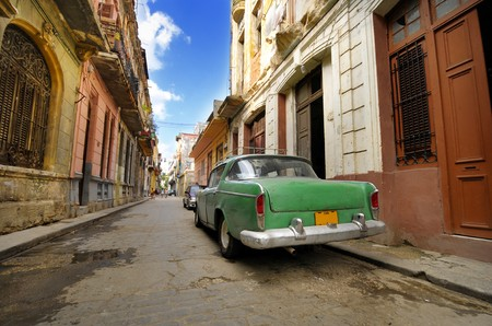 Vintage car parked in shabby Old Havana street with crumbling facades