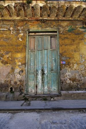 crumbling: Green rustic door over crumbling walls in eroded building facade in Old Havana, Cuba.