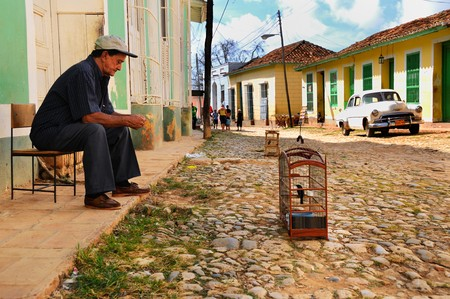 Bird cage and old man sitting in a street of Trinidad, Cuba. It was declared by UNESCO World Heritage Site in 1988. Taken circa OCT 2008.