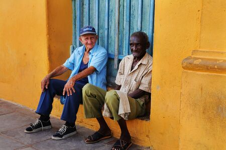 declared: Two senior men sitting in colorful Trinidad street. It was declared by UNESCO World Heritage Site in 1988. Taken circa OCT 2008.