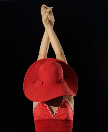 Portrait of woman in red wearing hat against black background with raised arms photo