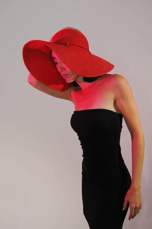 Portrait of young stylish woman on black dress wearing a hat photo