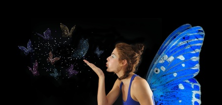 Fairy with blue wings blowing butterflies, isolated over black photo