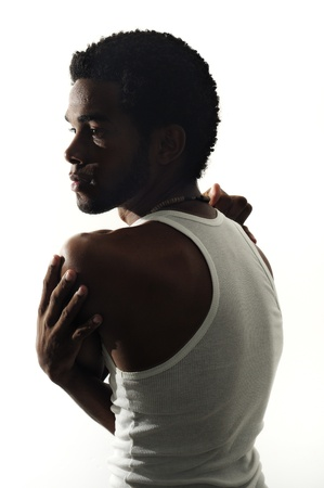 Low key portrait of young african american man posing isolated on white photo