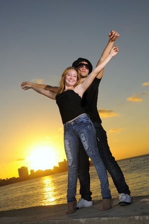 Portrait of young hispanic couple stading together against sunset background photo