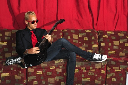 Yong male musician siting on red couch playing guitar photo