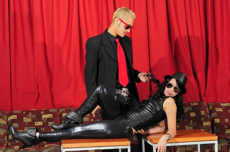 seductive women: Portrait of young hispanic couple dressed in black posing against red curtains Stock Photo