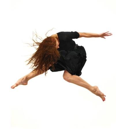 Hedendaagse danseres springen op wit wordt geïsoleerd