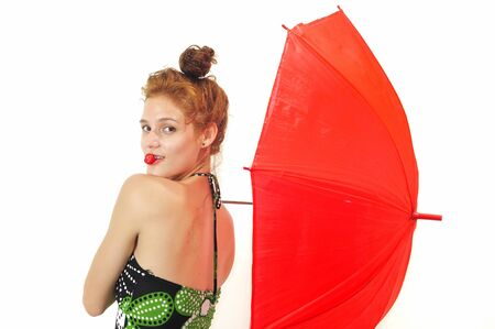 Portrait of young fresh beauty biting strawberry and holding red umbrella, isolated photo