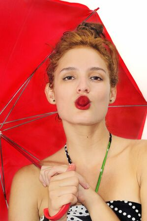 Portrait of fresh beauty biting strawberry and holding red umbrella isolated on white Stock Photo - 12924691