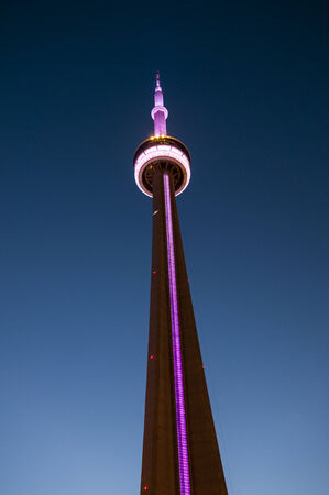 Detail of the CN Tower with violets lights in downtown Toronto at dusk