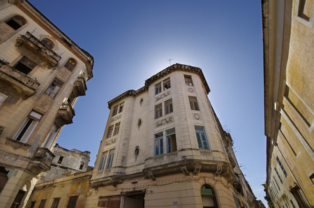 Vintage building facades in Old havana street against blue sky photo