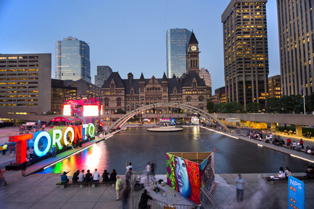 TORONTO,CANADA-JULY 9,2015: Panoramic view of the new Toronto sign in Nathan Phillips Square, host of PanaMania, a contant party celebrating the PanAm games. Old City Hall and downtown buildings in the back.