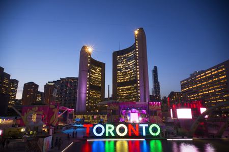 cityspace: TORONTO,CANADA-JULY 9,2015: The new Toronto sign in Nathan Phillips Square celebrating the PanAm games, the New City Hall at back. Stage have been mounted to held a constant party called Panamania