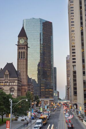 building structures: TORONTO,CANADA-JULY 9,2015: A view of Queen street in downtown toronto with Old City Hall building in the background, home to the city council from 1899 to 1966 and one of the citys most prominent structures. Editorial