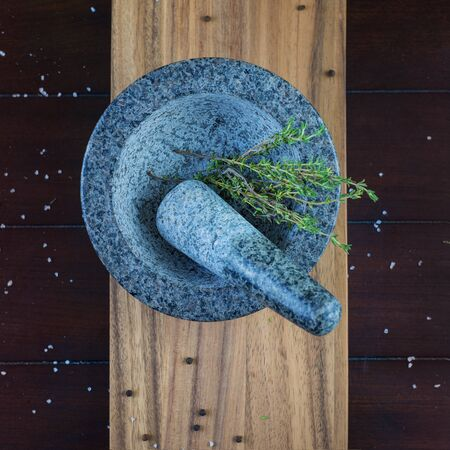 botanica: Granite stone mortar and thyme herb over wooden plank