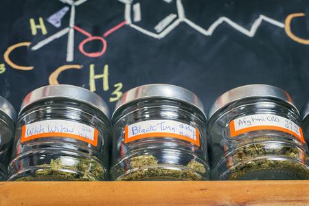 Medical marijuana jars against board with THC formula - cannabis dispensary background Stockfoto