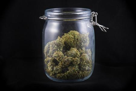 Cannabis bud in een glazen potten geïsoleerd op een zwarte achtergrond - medische marihuanaapotheek begrip