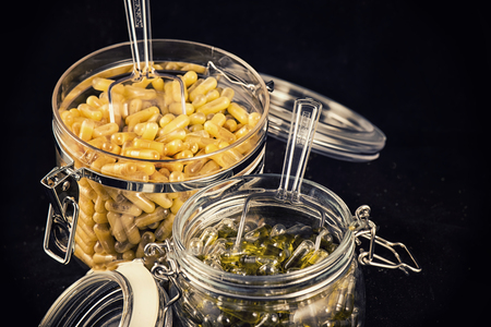 Jars with cannabis extraction capsules infused with shatter and cbd (marijuana compound) isolated over black background