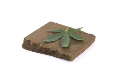 Block of hashish, a medical marijuana concentrate isolated on white with cannabis leaf Banco de Imagens