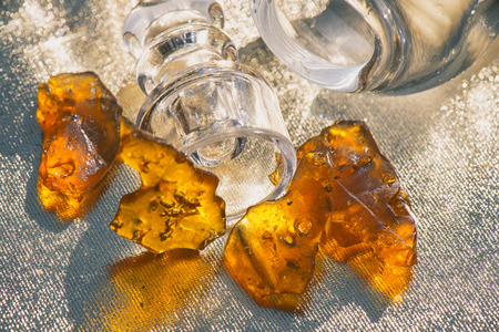 Pieces of cannabis oil concentrate aka shatter with glass rig over sparkling background Stockfoto