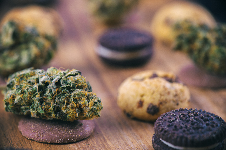 infused: Background with cannabis nugs over infused chocolate chips cookies - medical marijuana edibles concept Stock Photo
