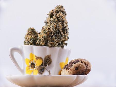 Detail van cannabis nug en koffiekop met chocolate chip cookies geïsoleerd over white - medische marihuana eetwaren begrip Stockfoto - 70564664