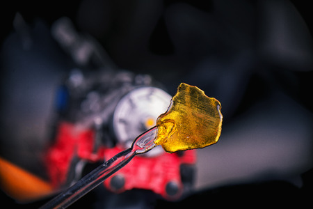 cannabinoid: Detail of cannabis oil concentrate aka shatter (train wreck strain) with dabbing tool against dark background
