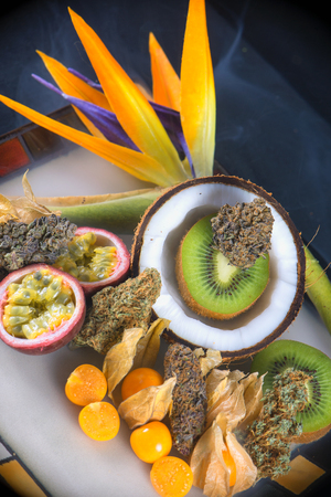 Detail of assorted dried cannabis buds with fresh tropical fruit - medical marijuana concept background