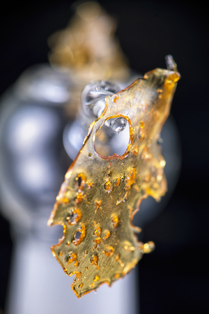 cannabinoid: Close up detail of marijuana oil concentrate aka shatter isolated on black background with glass rig and smoke