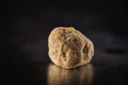 cannabinoid: Single piece of marijuana extraction concentrate aka wax crumble on dark background