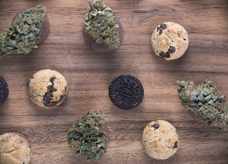 Background with cannabis nugs (forum cut cookies strain) over infused chocolate chips cookies - medical marijuana edibles concept 스톡 콘텐츠