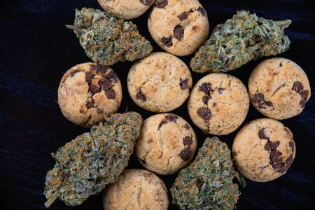 Background with cannabis nugs (forum cut cookies strain) and infused chocolate chips cookies - medical marijuana edibles concept