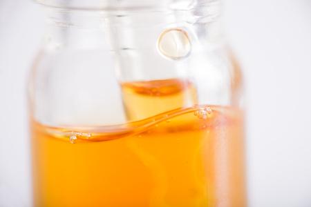 Macrodetail van container met CBD-olie, hennepextractie van cannabis levende op wit wordt geïsoleerd - medisch marihuanaconcept