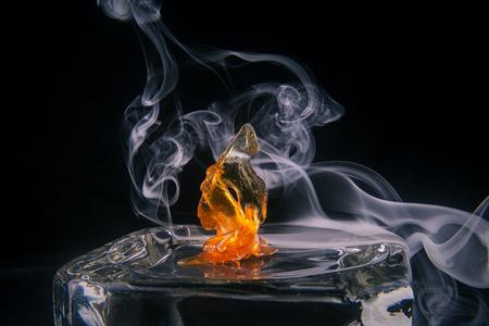 Geschmolzenes Hanfölkonzentrat alias Zersplitterung mit dem Rauch lokalisiert über dunklem Hintergrund