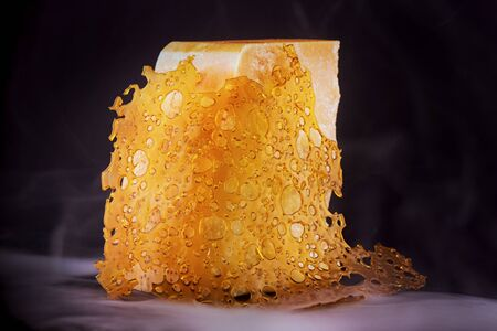 Close up detail of cannabis oil concentrate aka shatter with cheese block isolated over black with smoke - medical marijuana edible concept