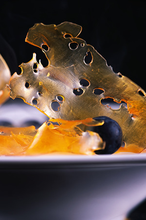 Macro detail of cannabis oil concentrate aka shatter against dark background with blue berries