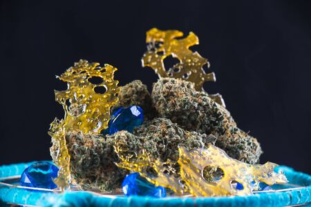 Macro detail of cannabis nugs and marijuana concentrates (aka shatter) with smoke isolated over black Banco de Imagens