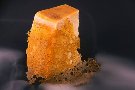 Close up detail of marijuana oil concentrate aka shatter over cheese block on black background with smoke