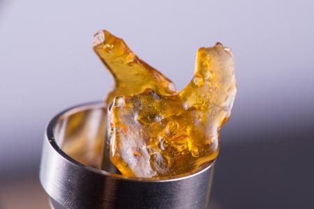 Makro Detail des Stückes von Cannabisöl Konzentrat aka Splitter auf einem Titan dab rig Standard-Bild - 84343309