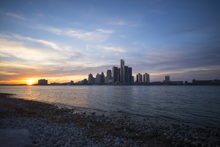 View of Detroit city skyline at sunset from the shore of the river on the canadian side
