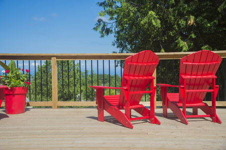 typical: View of 2 empty red muskoka chairs on a wood deck, ready to enjoy the view in the canadian summer