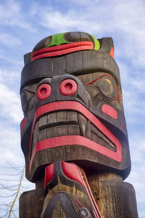 View of ancient colorful Totem Pole with blue sky behind it in Duncan, British Columbia, Canada. Stock Photo