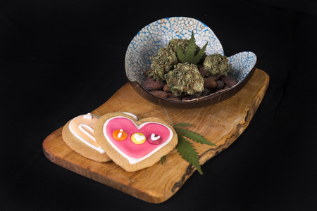 Dried cannabis nugs with cacao beans and baked cookies on a tray - infused marijuana edibles concept Stock Photo