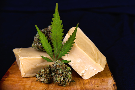 Detail of wood tray with Cannabis infused fudge isolated on black - medical marijuana edibles concept