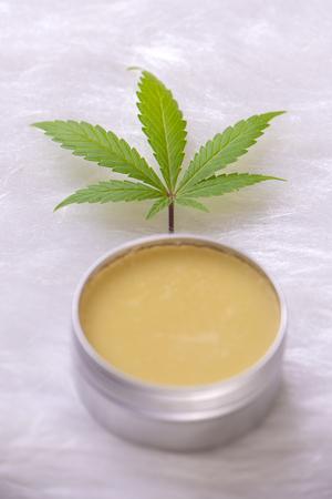 Cannabis hemp cream with marijuana leaf over white background - cannabis topicals concept Stock Photo