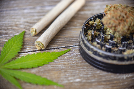 Cannabis joints with rolling paper and grinder over wood background 写真素材