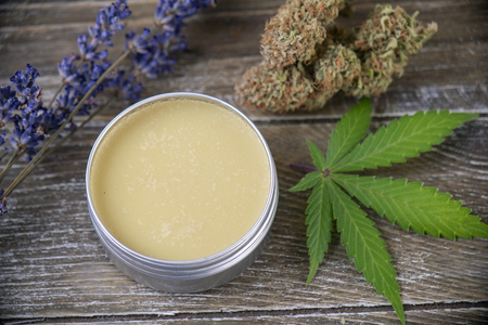 Crema di canapa alla cannabis con foglie di marijuana, lavanda e cime su fondo di legno - concetto di argomenti di cannabis