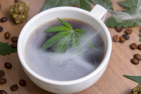 Detail of smoky cannabis coffee cup with beans, nugs and marijuana leaves, marijuana edibles concept